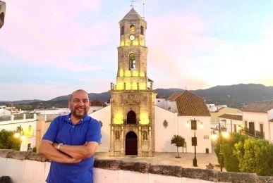El párroco Yelman Bustamante posando delante de la iglesia de San Isidro Labrador