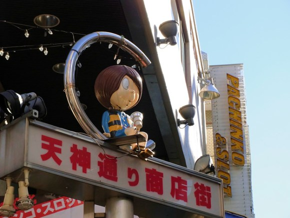 """Tenjin Street is a shopping street that lines the sandō (approach) to Fuda Tenjin Shrine. The street is lined with characters from the anime """"Gegege no Kitarō."""""""