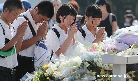 Personas rezando en el acto de homenaje a las víctimas de la bomba atómica de Hiroshima