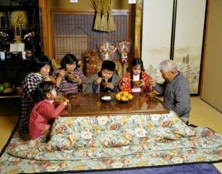 """Familia japonesa cenando en torno a un """"kotatsu"""" o mesa con calefacción"""