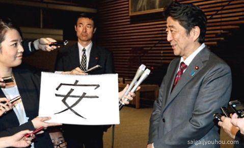 """Shinzo Abe recibiendo un papel con el carácter """"yasu"""" (kanji del año 2015)"""