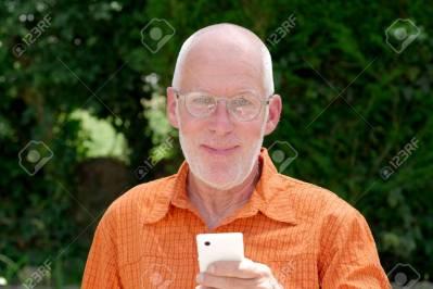 80533427-un-homme-senior-en-bonne-santé-au-téléphone-jardin-extérieur-min