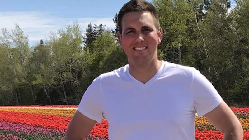 Basatiaan Arendse, copropriétaire de VanCo Farms, devant un champ de tulipes rouges, roses, jaunes et orange.