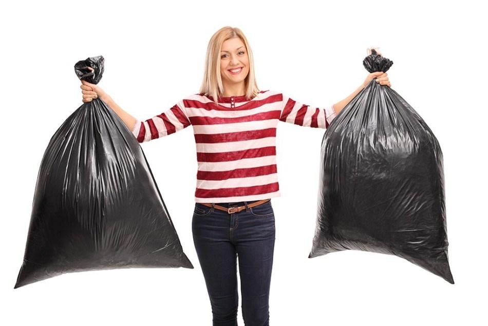 Femme tenant 2 sacs de poubelles pleins.