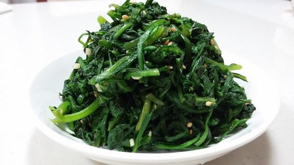Feuilles de chrysanthème couronné après cuisson. Vert foncé, lisses, dans un bol blanch.