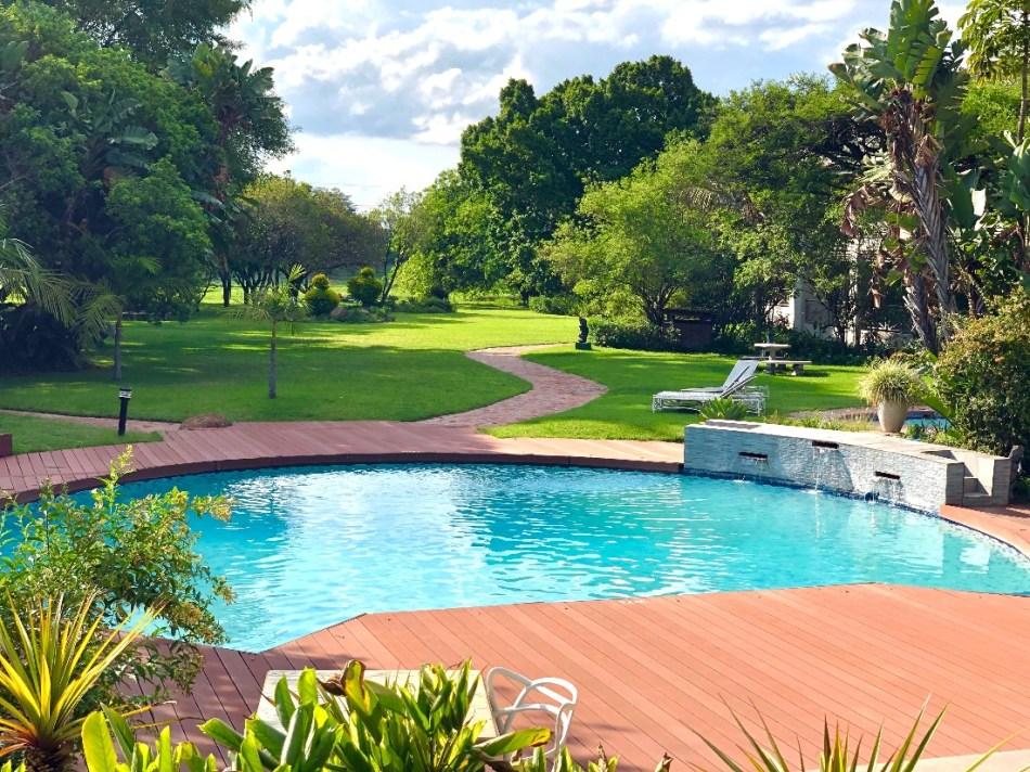 Terrasse en bois avec piscine aux contours arrondis, entourée de pelouse verte.