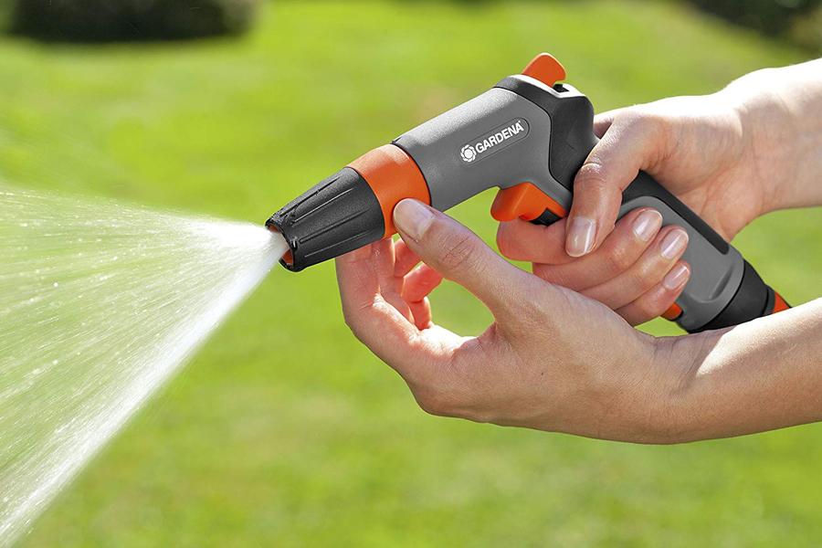 Main qui ajuste le volume d'eau d'un pistolet d'arrosage.