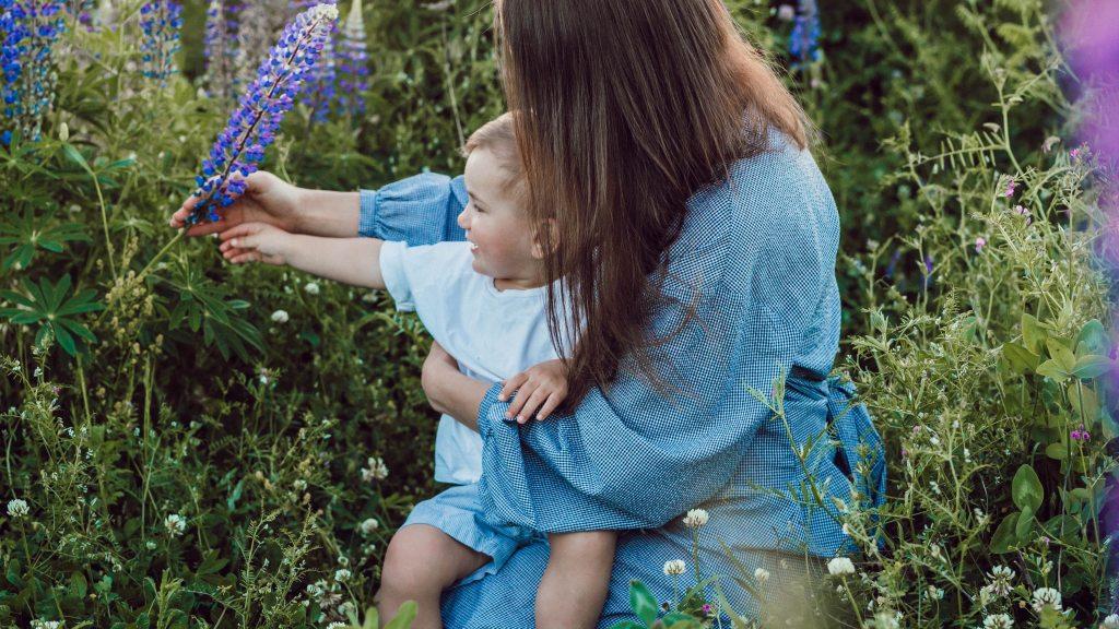 Femme et bébé dans un champ de lupins.