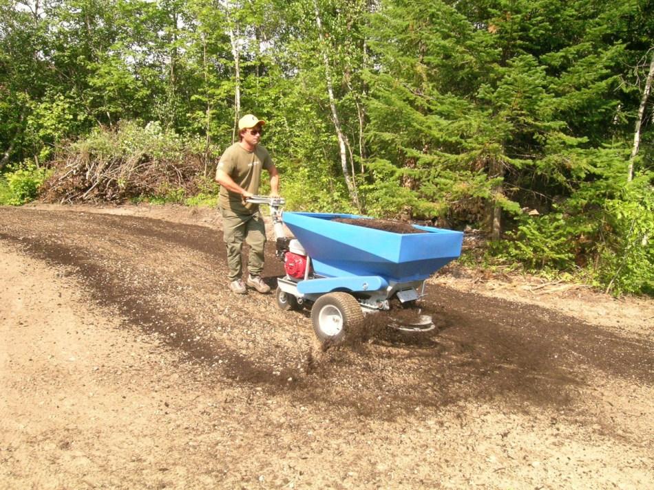 Un terreauteur motorisé appliquant du compost sur un champ.
