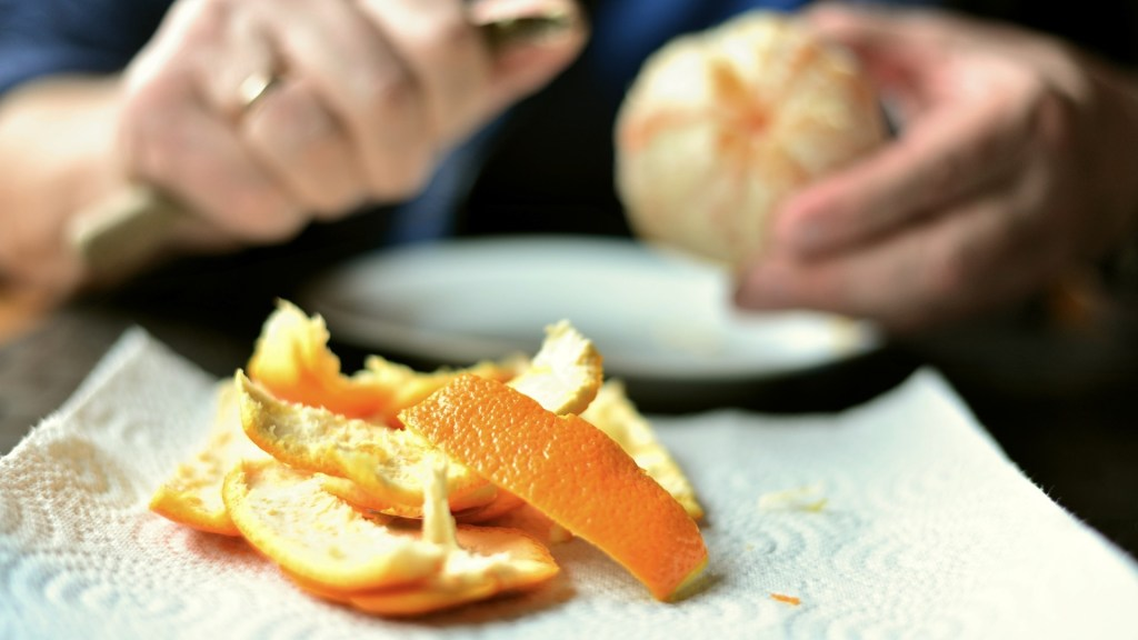 Pelures d'orange et main qui pêle une orange
