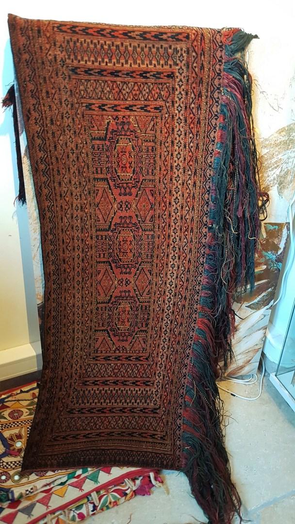 """Tapis de selle """"Torba"""" en velours de laine sur chaîne en laine ; tissage traditionnel fait à la main et frange longue en laine (Fin 19ème siècle), OUZBEKISTAN - Dimension : 127 cm x 32 cm - Prix de vente : 850€."""