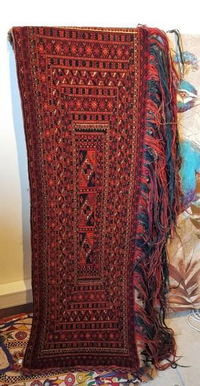 """Tapis de selle """"Torba"""" en velours de laine ; tissage traditionnel fait à la main et frange longue en laine (Fin 19ème siècle), TURKMENISTAN - Dimension : 125 cm x 40 cm - Prix de vente : 1200€."""