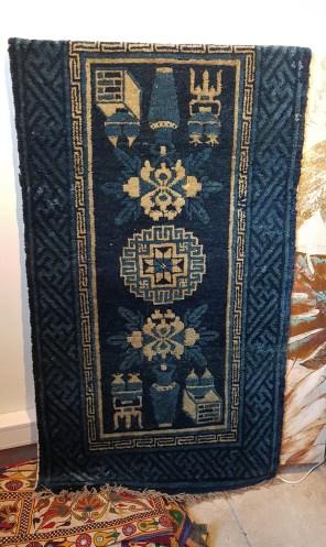"""Tapis """"Pao Tao"""" en laine ; à médaillon central décoré de vases et de meubles sur fond bleu, tissage traditionnel fait à la main avec jute (Fin 19ème siècle), CHINE - Dimension : 120 cm x 62 cm - Prix de vente : 690€."""