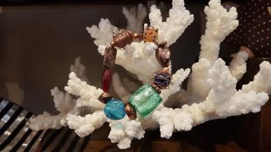 Bracelet en perle de verre teintée serti de breloques en métal, INDE - Prix de vente : 15€.