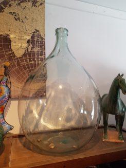Dame Jeanne ou Tourie en verre non teinté soufflé dans un moule, ITALIE – Dimension : 69 cm haut x 45 cm large – Litrage : 54 litres – Prix de vente : 150€.