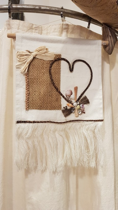 Pendant en coquillage et raphia cousu sur toile en coton, INDONÉSIE - Prix de vente : 10€.