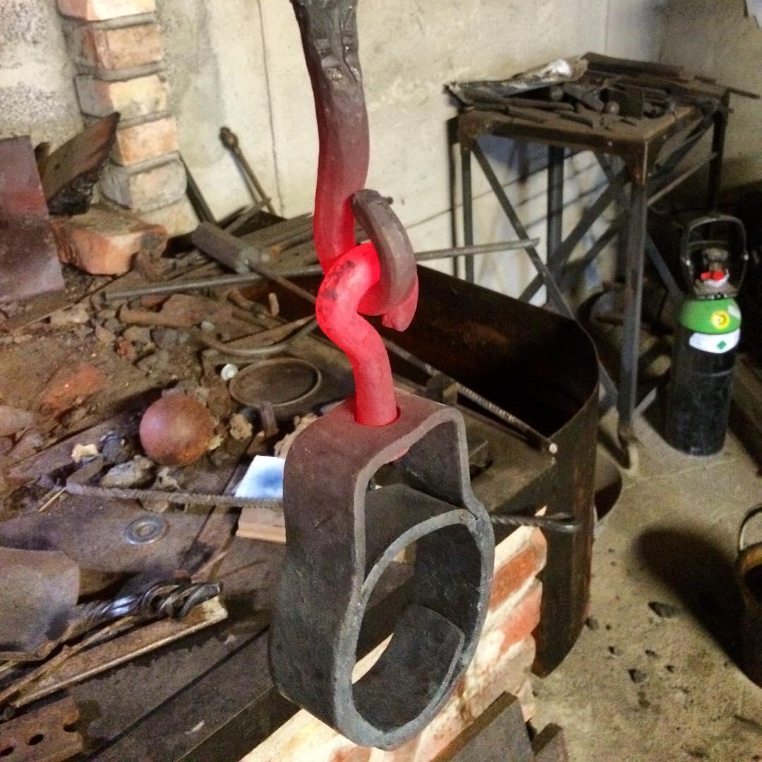 Brunnsjong/klyka, ny upphängning till brunnsarmen efter existerande förlaga som var aningen utsliten. Vällda skarvar till krokgenomföringen. ?? Forged hinge and coupler for an old well, seams are forge welded for the lower hook coupler