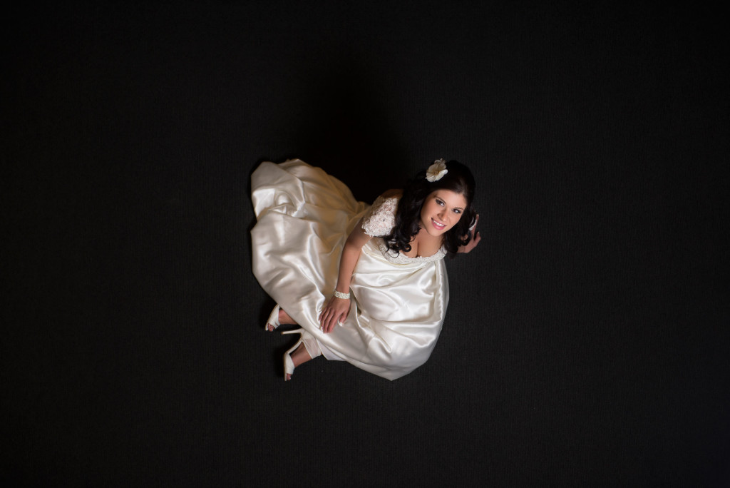 Bride sitting on a dark carpet looking up.