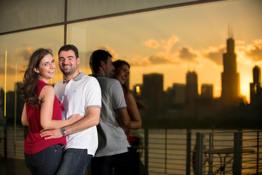 Couple leaning against the glass with city reflections during sunset