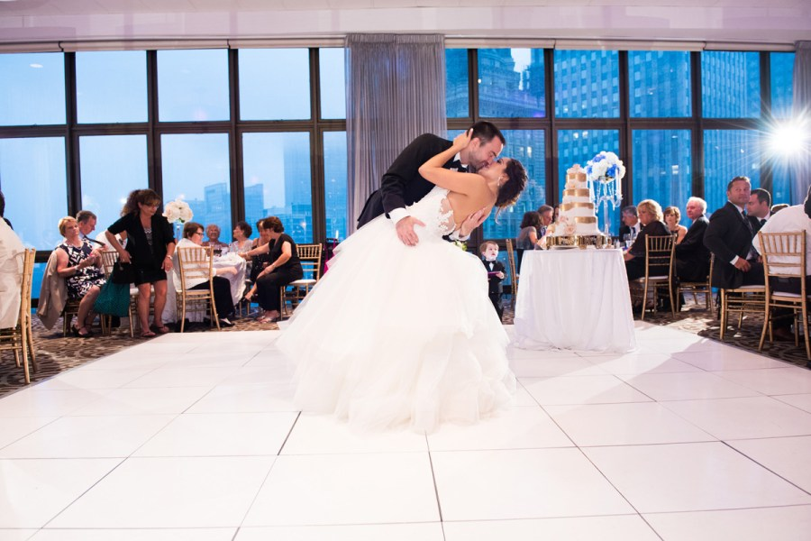 bride and groom dip during wedding reception first dance kissing