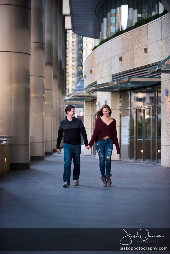 Engaged Couple Walking with pillars in the background