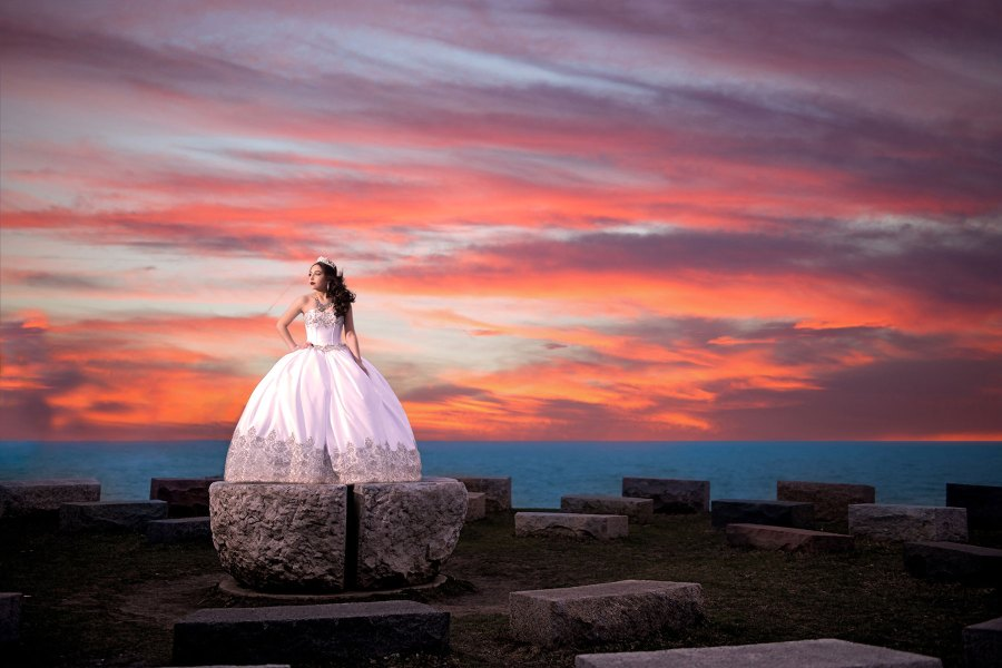 bride standing on the rock before beautiful sunset skies in Chicago