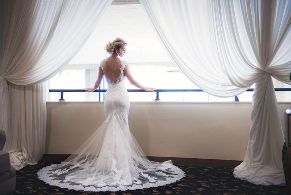 bride standing with a back photograph of her lace wedding dress