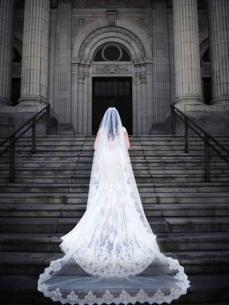 Bride Walking Up The Stairs of The Church With Her Long Veil