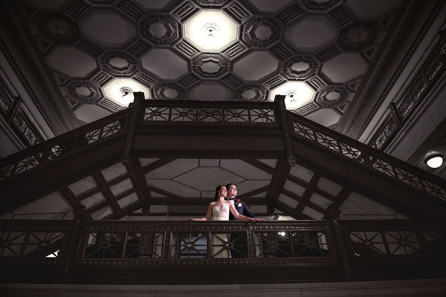 Bride and groom at standing on a staircase of Chicago Cultural Center on their wedding day.