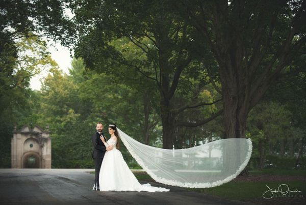 Bride and Groom at the Park with brides veil flying of into the wind