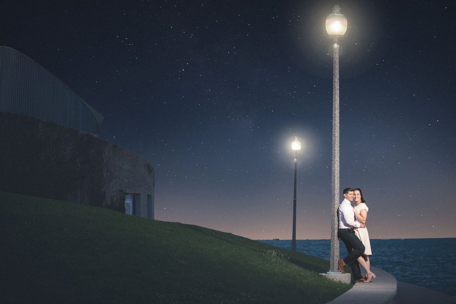 a dreamy engagement photography image of a couple leaning on a light poll before night skies with stars.
