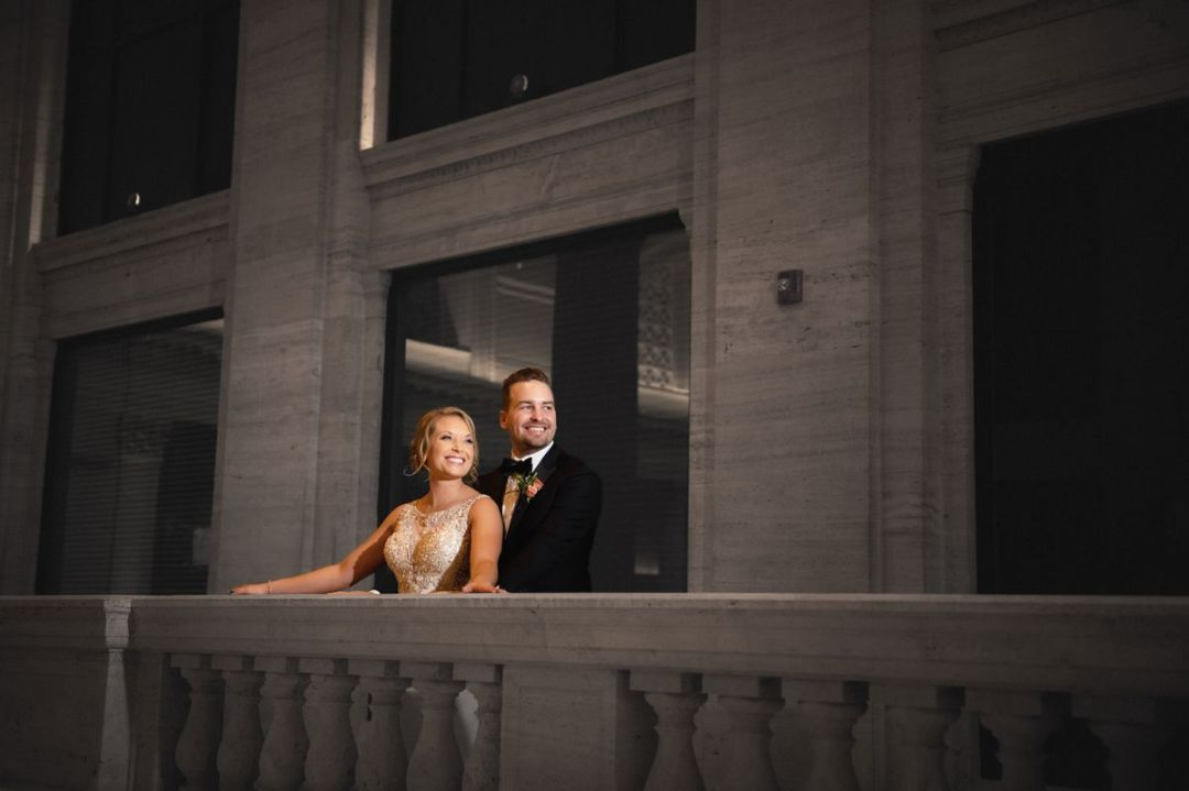 bride and groom standing at the balcony of union station in chicago