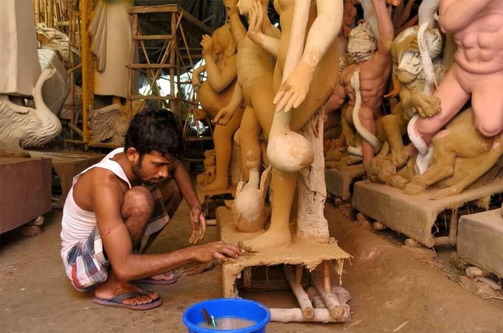 An artisan adds finishing touches to the raw clay idol of Goddess Saraswati. Image ©2017 Jasmine Trails