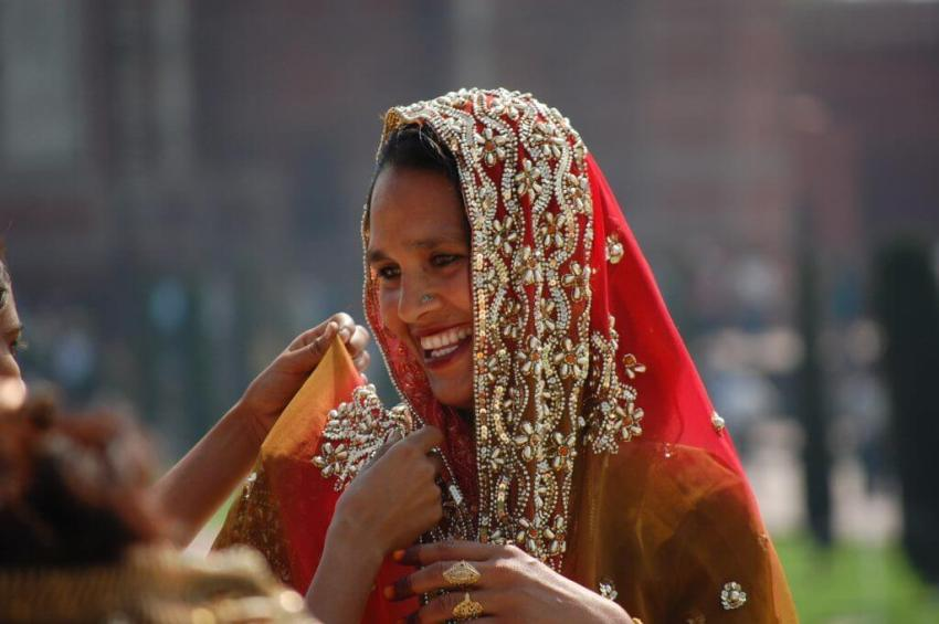 Woman Traveler. An Indian lady in bridal finery in front of Taj Mahal
