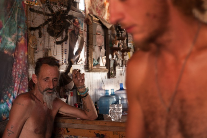 Spyder and his son, Daniel Wild, rest after building the pig pen at their family's camp, The California Ponderosa. Slab City, California 2018