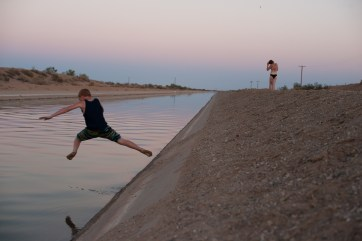 Families risk arrest and drowning in swift currents to swim in the cool waters of a nearby canal. Slab City, California 2018