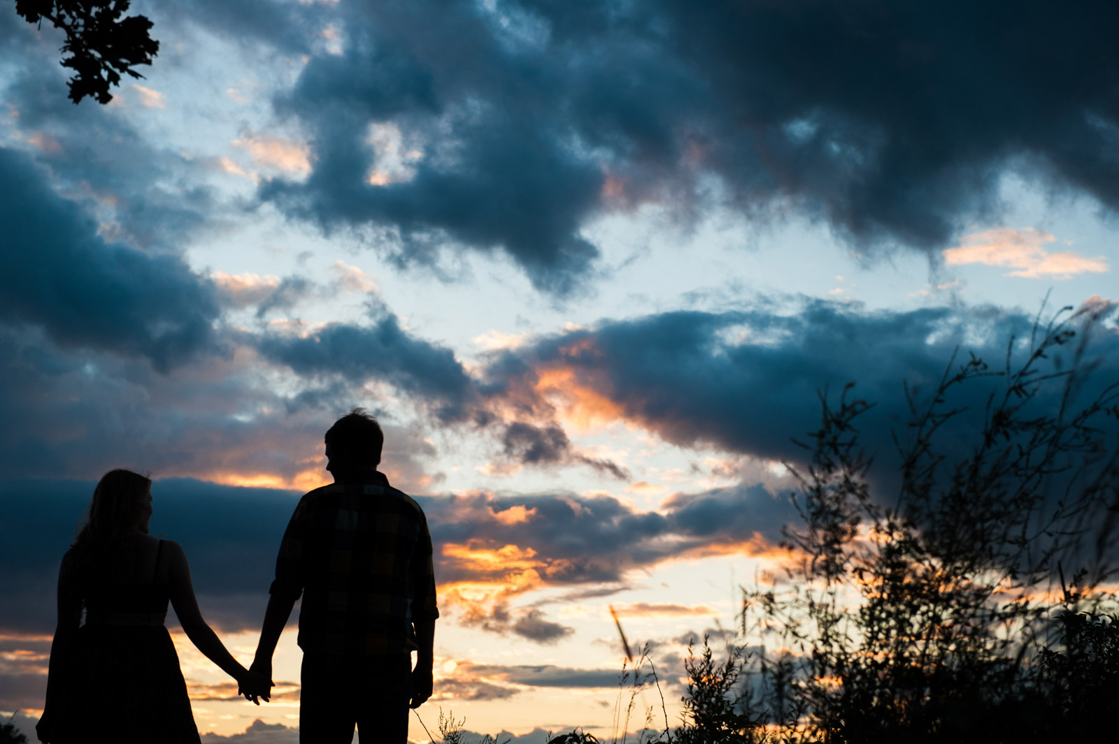 Engagement Session couple holding hands in silhouette at sunset