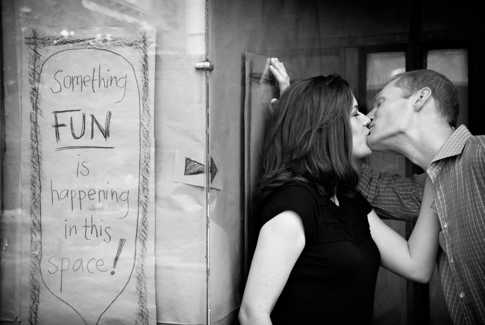 Funny engagement session next to sign that reads something fun is happening in this space of rented storefront