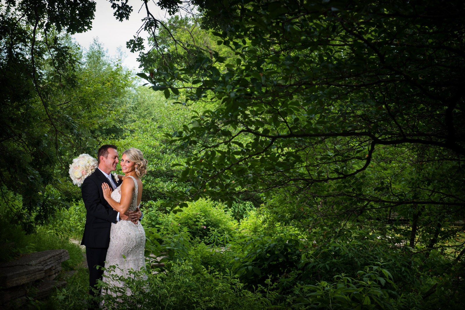 Dramatic Bride and Groom photo in nature surrounded by trees and lush vegetation