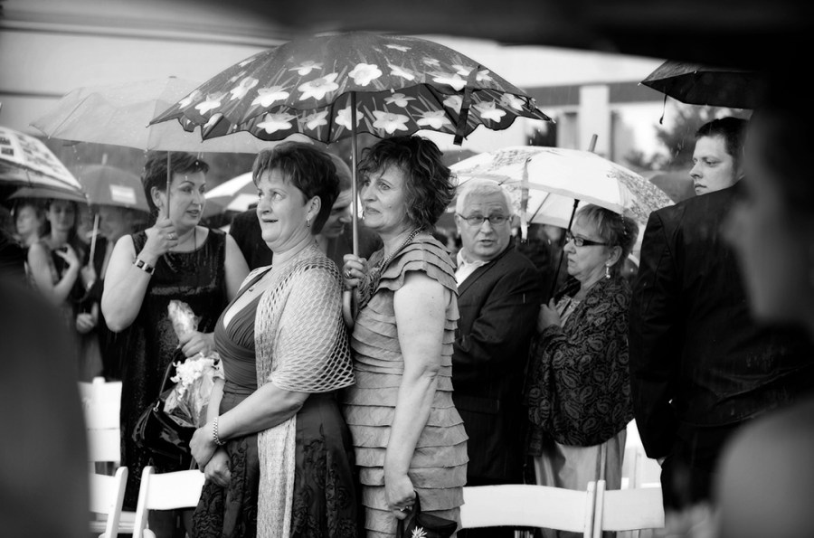 Wedding Guests under umbrella in rain at ceremony