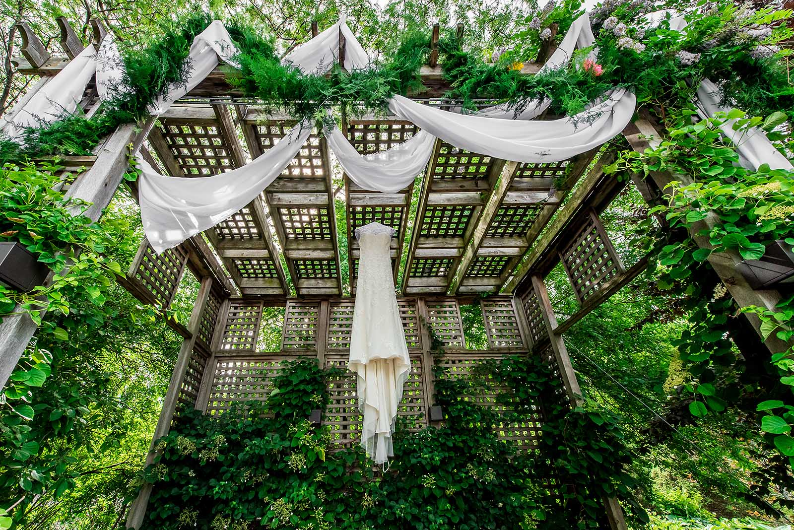 Wedding Dress hanging outdoors in garden pergola