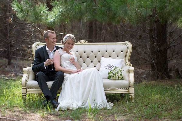 bride and groom sitting on vintage furniture in forest near Bright Victoria