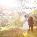 bride and groom under tree in sunlight