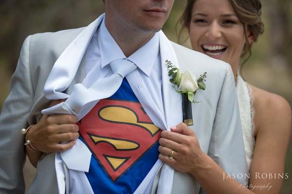 bride with groom showing superhero shirt under wedding suit