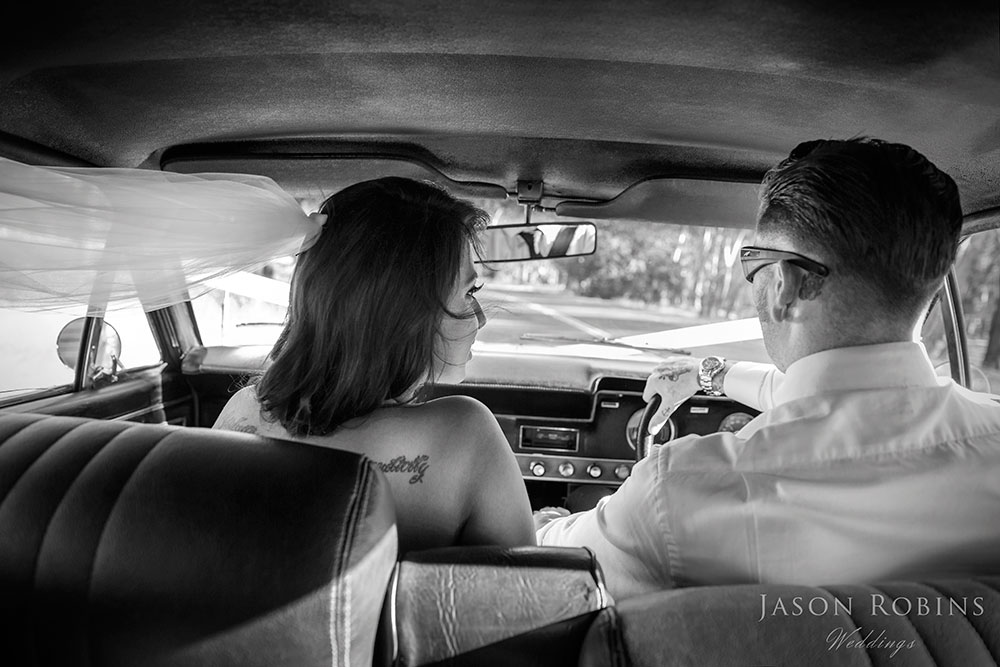 Black and White image of bride and groom in bridal car