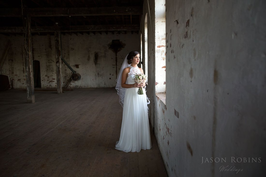 Bride looking out window at old mill