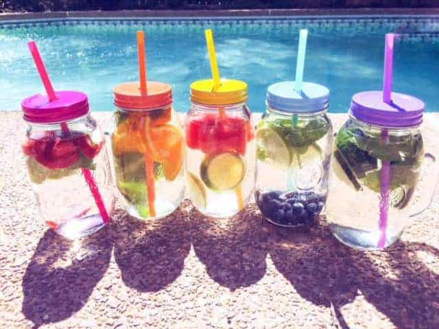 infused water recipes in cups sitting by a pool