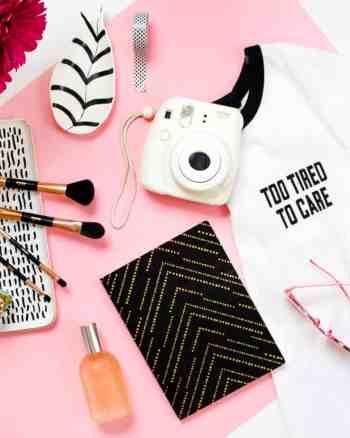 t-shirt camera and makeup brushes flatlay