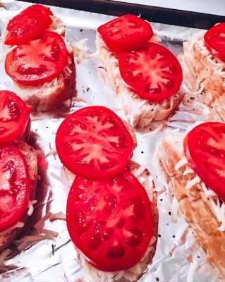caprese crostini with tomatoes on baking sheet