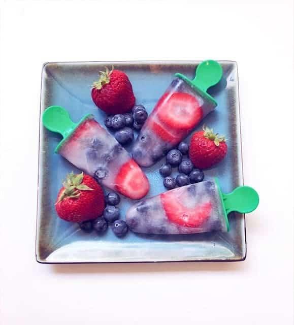 homemade fresh fruit popsicles on plate with fresh fruit